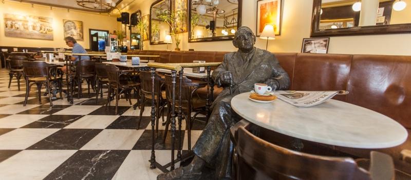 Imagen frontal de la estatua de Torrente Ballester en el Café Novelty